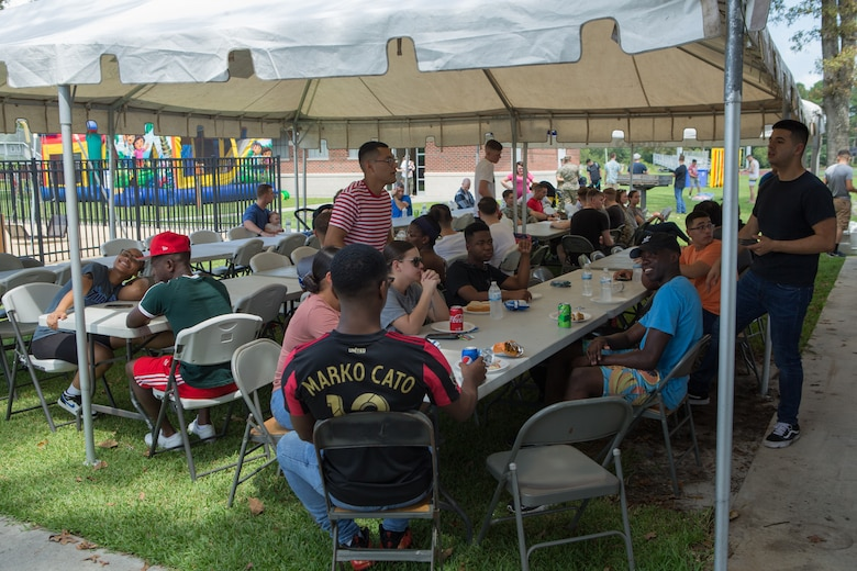 U.S. Marines and Sailors from Marine Wing Headquarters Squadron 2 eat some food during the unit's Family Fun Day at Marine Corps Air Station Cherry Point, North Carolina, August 20, 2019. The MWHS-2 Family Fun Day was hosted to give Marines and Sailors some time to meet and build camaraderie throughout the unit. (U.S. Marine Corps photo by Pfc. Steven Walls)