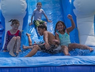Children race down a water slide during the Marine Wing Headquarters Squadron 2 Family Fun Day at Marine Corps Air Station Cherry Point, North Carolina, August 20, 2019. The MWHS-2 Family Fun Day was hosted to give Marines and Sailors an opportunity to socialize and build camaraderie throughout the unit.  (U.S. Marine Corps photo by Pfc. Steven Walls)