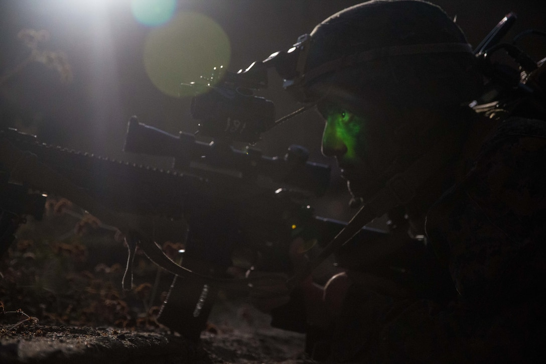A Marine on the ground with a rifle scopes out a target using night vision.