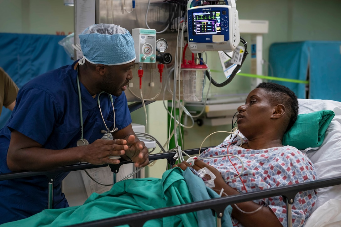 A nurse talks to a patient in a hospital bed.