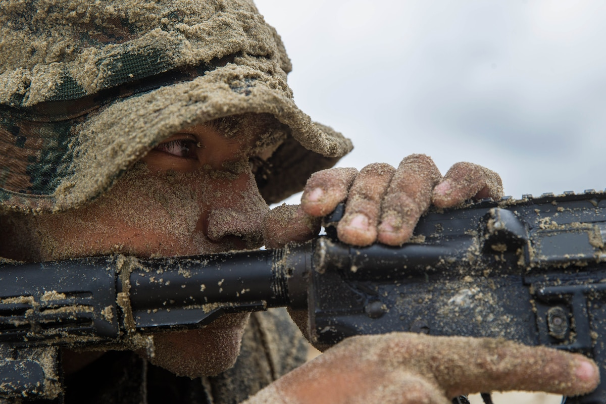 A close up of a sand-covered Marine with a rifle.