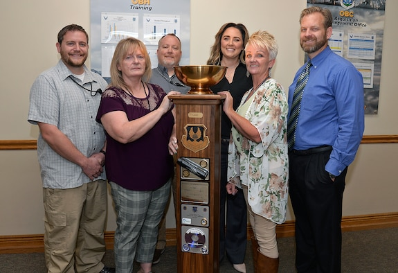 Britt Bush, Joan Young, Jacob Beyer, Brittney Starnes, Michelle Broderick and Benjamin Orton, Business Operations Workloading Chief, pose with the Ogden Air Logistics Complex L-A-M-P Award trophy Sept. 10 at Hill Air Force Base, Utah.