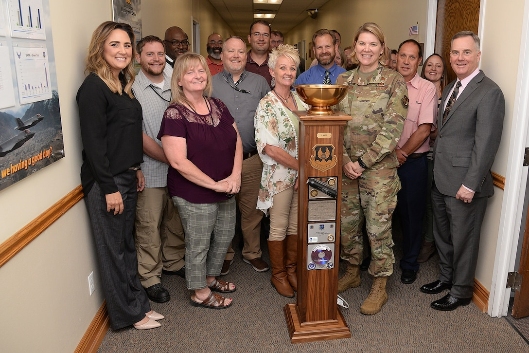 Ogden Air Logistics Complex leadership and the ALC's Business Operations Workload Management team pose with the  L-A-M-P Award trophy Sept. 10, 2019, at Hill Air Force Base, Utah. The award is a traveling trophy presented each month to the ALC's most outstanding unit or team. (U.S. Air Force photo by Alex R. Lloyd)