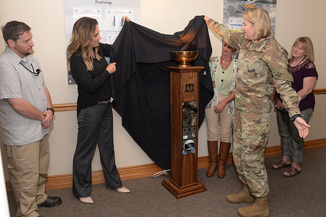 Brittney Starnes, Business Operations Workload Management chief (left), helps Brig. Gen. Cauley von Hoffman, Ogden Air Logistics Complex commander, unveil the L-A-M-P Award trophy Sept. 10, 2019, at Hill Air Force Base, Utah. The award is a traveling trophy presented each month to the ALC's most outstanding unit or team.(U.S. Air Force photo by Alex R. Lloyd)