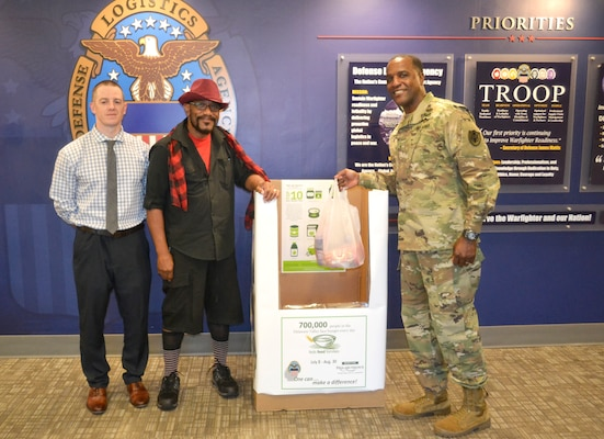Army Brig. Gen. Gavin Lawrence, DLA Troop Support commander, right, Leonard Shannon, DLA Troop Support material handler, center, and Shaun Eagan, DLA Troop Support public affairs specialist, pose in front of a Feds Feed Families donation box Sept. 3, 2019 at DLA Troop Support in Philadelphia.