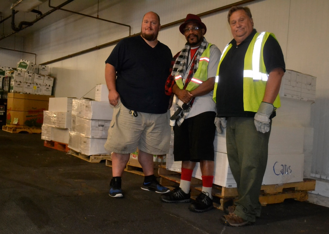 Steve Riecky, a Philabundance warehouse employee, left, and DLA Troop Support material handlers Leonard Shannon, center, and James Burke, right, pose for a photo at the Philabundance warehouse Sept. 13, 2019 in Philadelphia.
