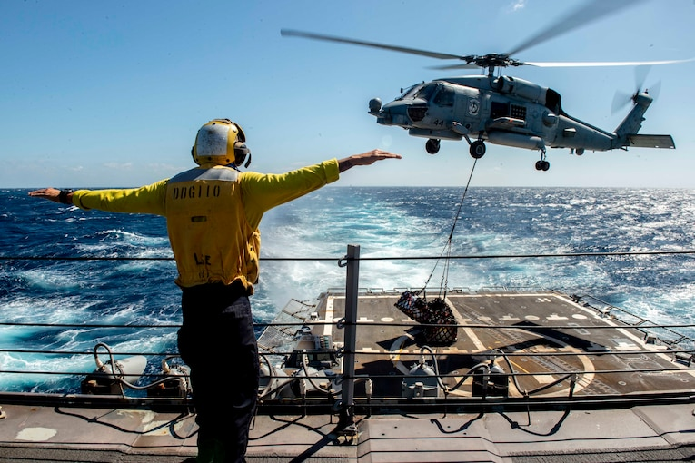 A sailor hold his arms out as a helicopter hovers above a military ship.