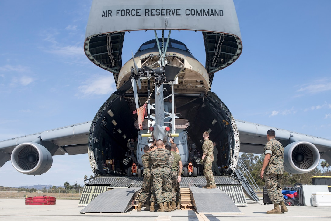 U.S. Marines and airmen assist in loading a UH-1Y Venom into C-5M Super Galaxy at Marine Corps Air Station Camp Pendleton, California, Sept. 16, 2019. The C-5M was a visiting U.S. Air Force aircraft from 433rd Airlift Wing, and was here as part of a dual service training exercise.The air station provides the 1st Marine Expeditionary Force and 3rd Marine Aircraft Wing with flexible deployment options. (U.S. Marine Corps photo by Lance Cpl. Drake Nickels)