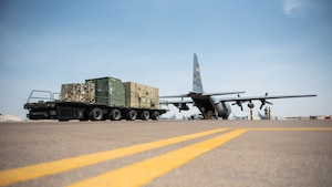 380th Expeditionary Logistics Readiness Squadron air transportation specialists prepare to load a C-130 Hercules Sept. 17, 2019, at Al Dhafra Air Base, United Arab Emirates. The Air Transportation Operations Center enables Airmen to travel and fulfill duty requirements and taskings throughout the area of responsibility. (U.S. Air Force photo by Staff Sgt. Chris Thornbury)