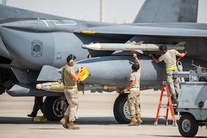 Weapons load crew members arm the munitions on an F-15E Strike Eagle before flight for Agile Strike Sept. 18, 2019, at Al Dhafra Air Base, United Arab Emirates. The 336th EFS sent two aircraft and personnel to operate missions out of Prince Sultan Air Base, Saudi Arabia to challenge their flexibility at expanding tactical and strategic reach while strengthening coalition and regional partnerships in the Air Forces Central Command area of responsibility through adaptive basing. (U.S. Air Force photo by Staff Sgt. Chris Thornbury)