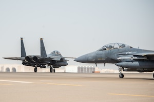 Two F-15E Strike Eagles, assigned to the 336th Expeditionary Fighter Squadron, taxi before flight for Agile Strike Sept. 18, 2019, at Al Dhafra Air Base, United Arab Emirates. The 336th EFS sent two aircraft and personnel to operate missions out of Prince Sultan Air Base, Saudi Arabia to challenge their flexibility at expanding tactical and strategic reach while strengthening coalition and regional partnerships in the Air Forces Central Command area of responsibility through adaptive basing. (U.S. Air Force photo by Staff Sgt. Chris Thornbury)