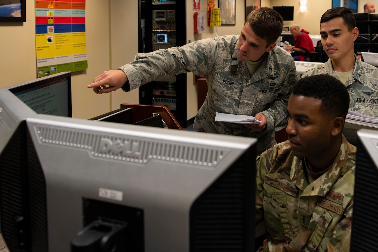 Three airmen look at monitors.