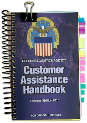 Isolated image of DLA Customer Assistance Handbook with large metal clip on top and multicolored tabs on the side.
