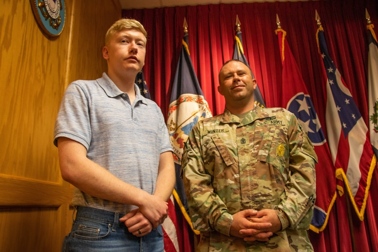 U.S. Army Pvt. 1st Class Michael Winter (left) stands next to father, 1st Sgt. Timothy Winter (right), while he waits to conduct his Oath of Enlistment Sept. 8, 2019 at the Beckley Military Entrance Processing Station, or MEPS, in Beckley, West Virginia. It is at this exact MEPS station where Timothy recited his Oath of Enlistment nearly 20 years ago.