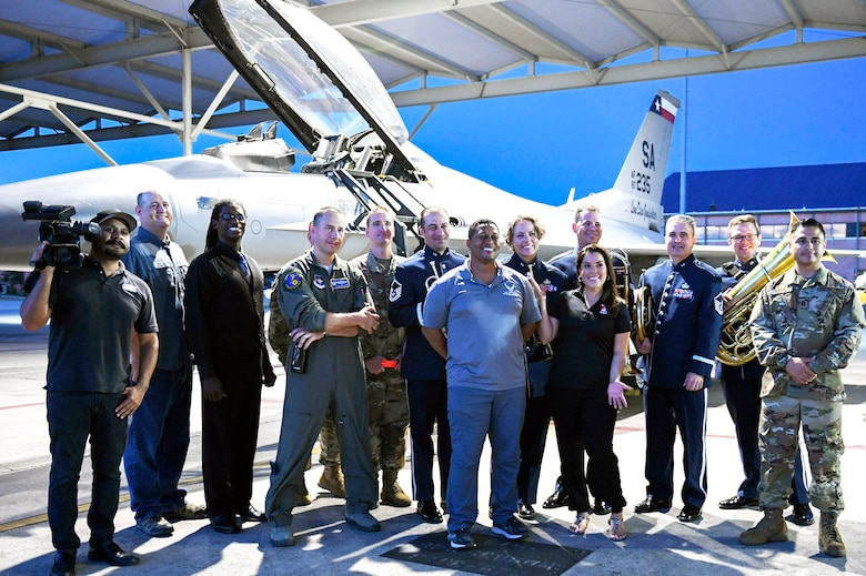 Members from Joint Base San Antonio-Lackland pose for a group photo in front of an F-16 Fighting Falcon, an aircraft sssigned to the 149th Fighter Wing, with local weather reporters Sept. 18 at JBSA-Kelly Field Annex in honor of the Air Force's 72nd birthday.