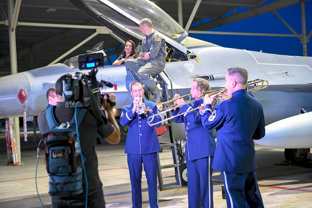 Members from United States Air Force Band of the West play in front of an F-16 Fighting Falcon, an aircraft assigned to the 149th Fighter Wing, while local weather reporter Jeannette Calle and 502nd Operations Support Squadron commander, Lt. Col. Benjamin Mather, talk in the background before the live broadcast at Joint Base San Antonio-Lackland Sept 18. Local weather reporters decided to conduct a live weather broadcast at the JBSA-Kelly Field Annex in honor of the Air Force's 72nd birthday.