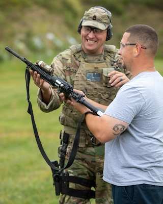 "Jerry Anthis, a service manager for Sinclair Fuel on Long Island, gets hints about the M-4 carbine from New York Army National Guard Sgt. 1st Class Fredrick Goldacker during a ""boss lift"" at Camp Smith Training Site in Cortlandt Manor, N.Y. on Monday, Sept. 16, 2019."