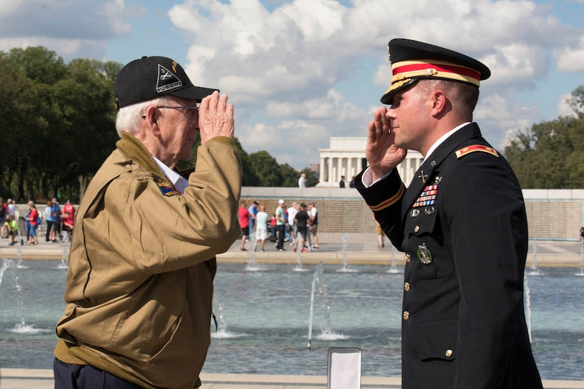 A soldier and a veteran salute each other.