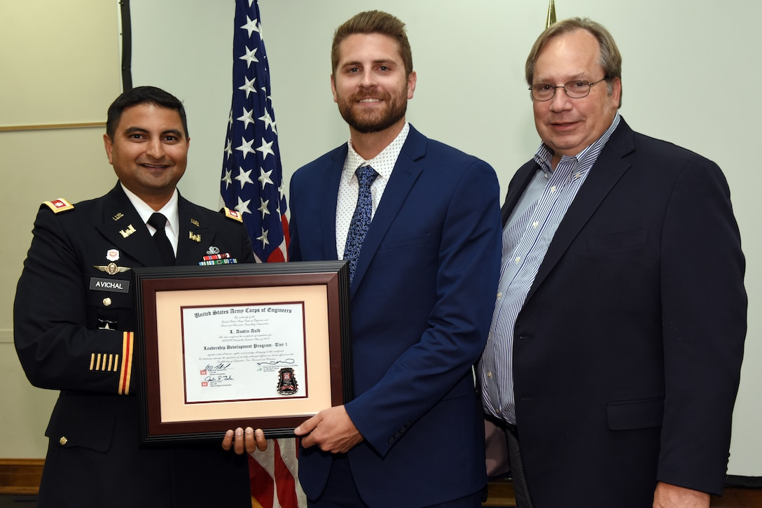 Austin Auld, U.S. Army Corps of Engineers Nashville District, receives a certificate of completion for the 2019 Leadership Development Program Level I Course from Lt. Col. Sonny B. Avichal, Nashville District commander, and Michael Evans, course instructor, during a graduation ceremony Sept. 12, 2019 at the Scarritt Bennett Center in Nashville, Tenn. (USACE Photo by Lee Roberts)