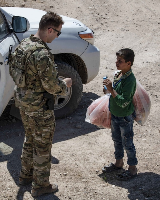 A service member speaks to a child.