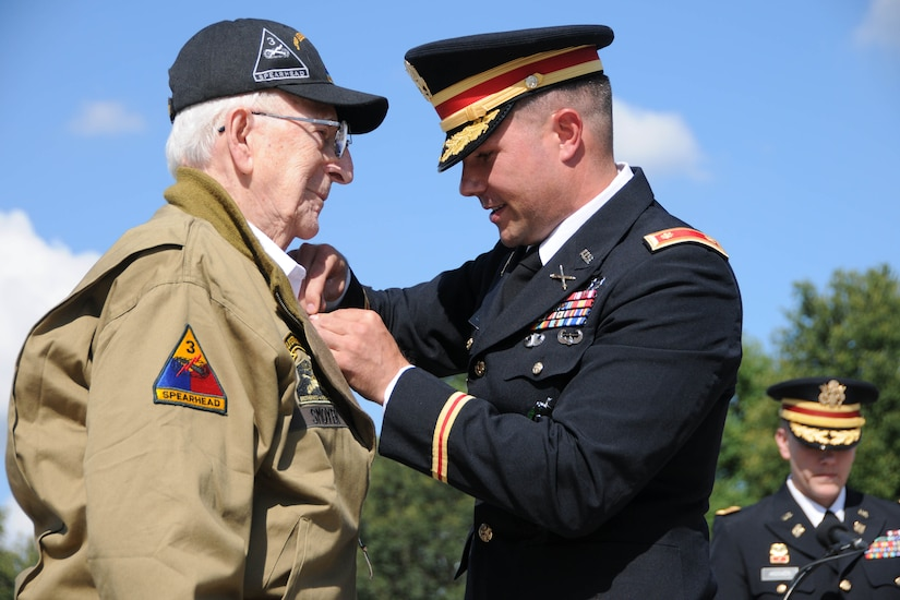 A man in a military uniform pins a medal to the lapel of another man in an outdoor location.