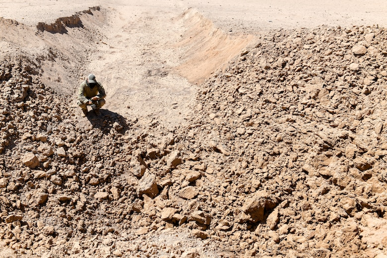 Staff Sgt. Jordan Jones, 56th Civil Engineer Squadron Explosive Ordnance Disposal team member, assigned to Luke Air Force Base, Ariz., inspects the aftermath of an explosion Sept. 12, 2019, at the Barry M. Goldwater Range near Gila Bend, Ariz.