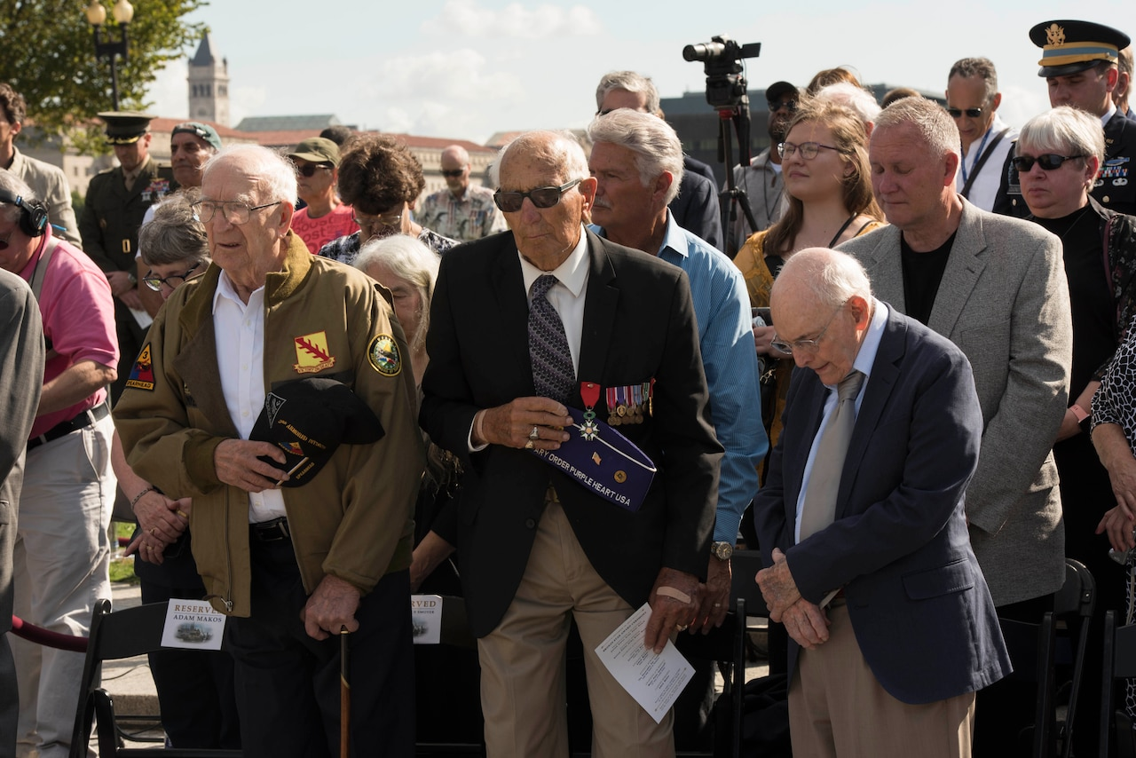 Three veterans stand together at an outdoor ceremony.