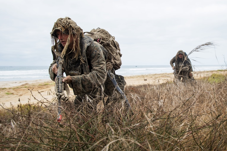 Two service members crouch and move forward on a beach.