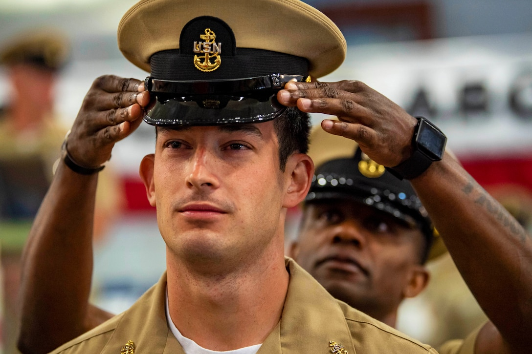A sailor places a hat on another sailor's head.