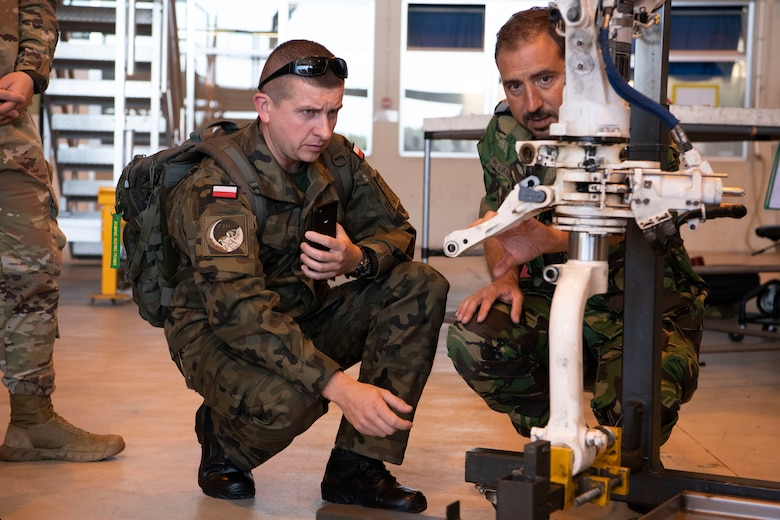 Polish Air Force Capt. Arkadiusz Kluba, discusses Portuguese F-16 operations with a Portuguese Air Force Master Sgt., during the European Partnership Flight at Monte Real Air Base, Portugal, Sept. 10, 2019. The European Partnership Flight serves as an opportunity for the U.S. and partner nations to share best practices, strengthen relationships, and build trust. (U.S. Army photo by Specialist Catessa Palone)