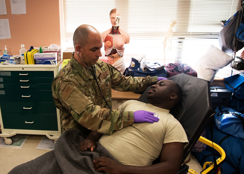 Tech Sgt. Simon Oliver, 459th Aeromedical Staging Squadron medical technician does training on Senior Airman Collin Owusu, 459th ASTS medical technician, Sept. 19, 2019, at Joint Base Andrews, Md. Oliver recently played a role in saving a passengers life while on a commercial flight to Jamaica. (U.S. Air Force photo by Staff Sgt. Cierra Presentado/Released)