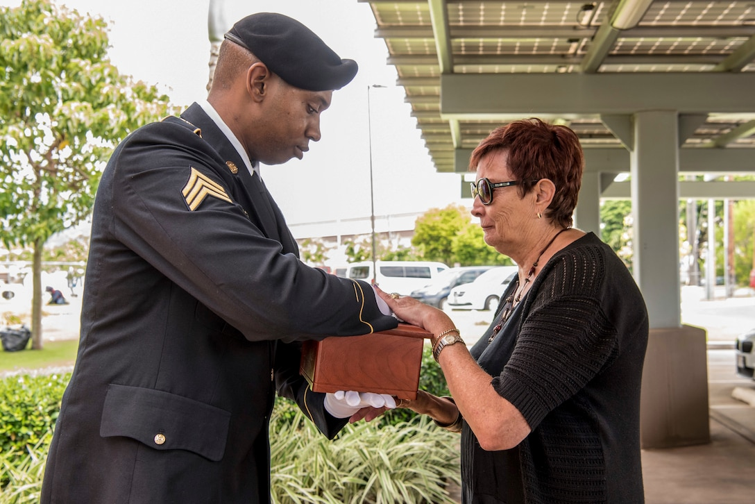 A soldier hands a box to a civilian woman.