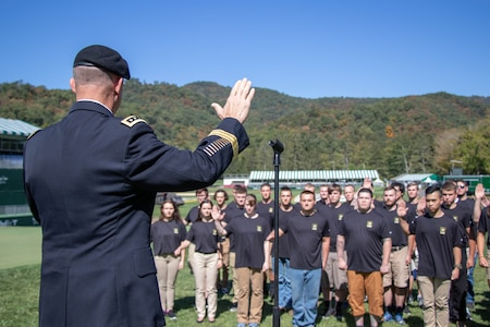 Older Army soldier raises his hand in front of large group of young teenagers in the middle of the valley.