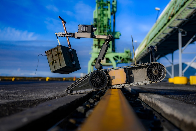 A robotic vehicle balances on a pier as it carries a heavy container.