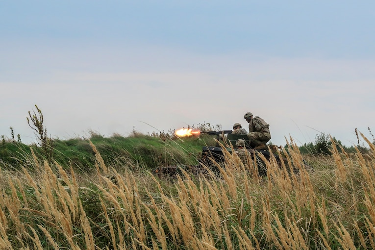 Soldiers fire a weapon from a vehicle in a field.