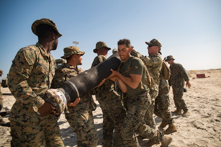 A group of Marines on a beach carry a large hose.