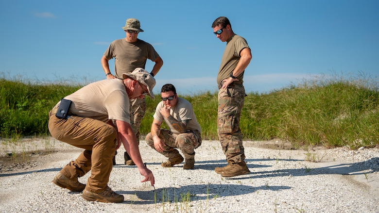 Maj. Brandon Ball, a Florida State Fire Marshal's Office bomb technician, draws a diagram of the planned circuit in the dirt to indicate the required set up for the simultaneous initiation of explosives at the Avon Park Air Force Range, Fla., Sept. 9, 2019. Federal, state and local authorities partnered to dispose of over 7,000 pounds of evidence following the conclusion of a federal case.