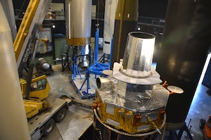 Photo of restoration crews moving a test satellite out of the missile gallery of the air force museum.