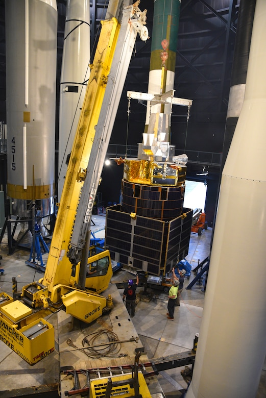 Photo of construction moving equipment and a test satellite in the missile gallery of the air force museum.