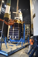 Photo of construction moving equipment and a test satellite.