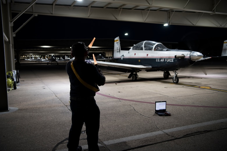 First Lt. Benjamin Peña and 1st Lt. Nicholas Myers, 85th Flying Training Squadron instructor pilots, place items inside a T-6A Texan II before takeoff on Sept. 18, 2019 at Laughlin Air Force Base, Texas. Night flying at a Specialized Undergraduate Pilot Training base allows not only more hours in the sky, but it also provides a variety experience so pilots can become accustomed to instrument flying. (U.S. Air Force photo by Senior Airman Marco A. Gomez)
