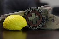 A brain-shaped stress ball and a 628th Medical Operations Squadron patch are displayed in front of an operational camouflage pattern cap at the mental health clinic Aug. 27, 2019, at Joint Base Charleston, S.C. Air Force medical technicians help ensure the medical readiness, both physically and mentally, of over 200,000 Airmen around the world.