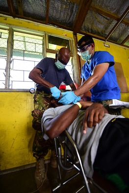 Papua New Guinea Defence Force Maj. Bais Gwale, a Pacific Angel 19-4 dentist, and U.S. Navy Petty Officer Victor Chiquete, a PAC Angel 19-4 dental technician, extract a patient's tooth at a health services outreach site in Lae, Papua New Guinea Sept. 9, 2019. Pacific Angel is multinational humanitarian assistance civil military engagement, improving military-to-military partnerships in the Pacific through medical health outreach, civic engineering projects and subject matter expert exchanges between U.S. service members, multinational militaries, non-governmental organizations, and PNG military and civilian participants. (U.S. Air Force photo by Tech. Sgt. Jerilyn Quintanilla)