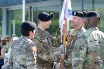 Capt. David Hilden, center-left, incoming commander, Houston Medical Recruiting Company, passes the guidon to 1st Sgt. Brian Filipowski, center-right, senior enlisted advisor, Houston MRC, during the company's change of command ceremony at Hermann Park Conservancy, Houston, Texas, Sept. 5.