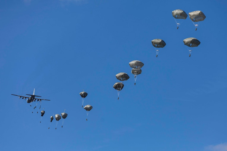 Service members jump from a plane in a line.