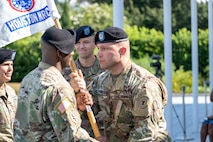 1st Sgt. Brian Filipowski, right, senior enlisted advisor, Houston Medical Recruiting Company, hands the company guidon to Capt. Ryan Sanders, left, outgoing commander, Houston MRC, during the company's change of command ceremony at Hermann Park Conservancy, Houston, Texas, Sept. 5.