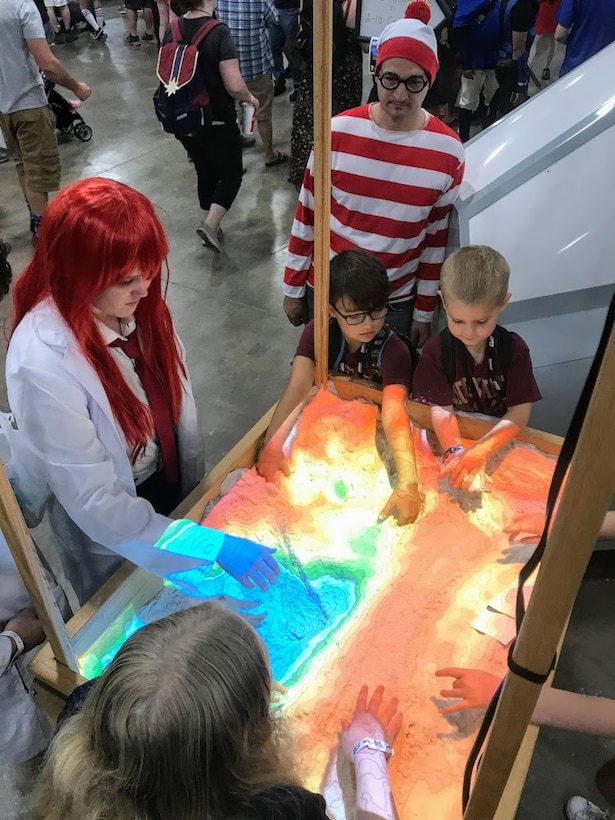 Participants at the 2019 FanX event play with a 3D interactive topographical map sandbox the Hill Air Force Base Science, Technology, Engineering and Math exhibit.  The event, which  was held at the Salt Palace Convention Center Sept. 5-7, drew thousands of visitors, providing great exposure for Hill and its STEM programs.