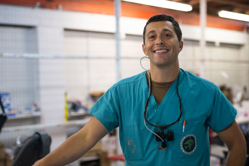 A Navy dentist wearing scrubs and stethoscope stands in a room and smiles.