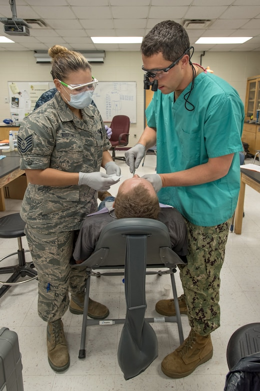 An Air Force dentist and Navy dentist stand on either side of a patient while performing a procedure.