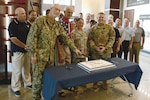 A group of people gathered around a cake celebrating the 72nd anniversary of the Air Force.